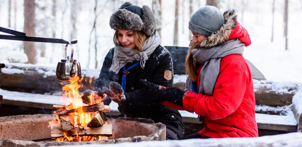 Valokuva: kaksi partiolaista nuotion äärellä talviretkellä